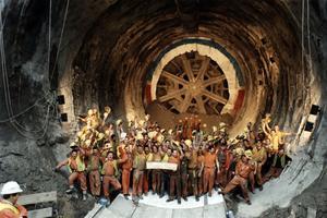 La construction du tunnel sous la Manche: les ouvriers avec leurs casques célèbrent la réalisation des trois tunnels entre la côte du Kent et le site terminal près de Folkestone en levant les bras, le 20 novembre 1990.
