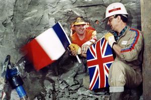 Philippe Cozette (à droite) de France et Graham Fagg d'Angleterre se serrent la main tout en tenant leur drapeau national respectif, lors de la percée finale du tunnel sous la Manche, au point de jonction des deux tunneliers, le 1er décembre 1990.
