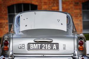 Un panneau en acier faisant office de bouclier se déploie de la malle arrière, permettant à James Bond de se protéger d'un tir nourri de balles.