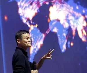 Alibaba founder and chairman Jack Ma gestures in front of a screen showing real-time data of transactions at Alibaba Group's 11.11 Global shopping festival in Beijing