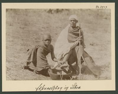 Un garçon lave dans un récipient en poterie les pieds d'un jeune noble assis sur un pliant.