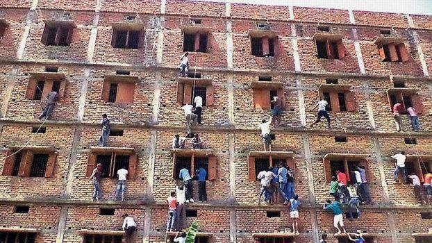 Accrochés aux fenêtres d'un centre d'examen, des indiens remettent des antisèches aux élèves passant les épreuves.