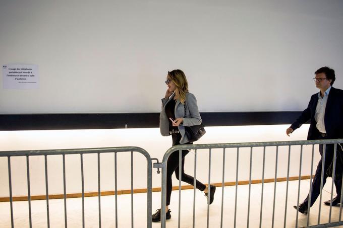 La jeune femme, téléphone à la main, marche rapidement dans les couloirs du tribunal.