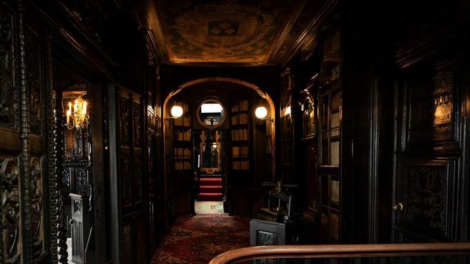 Des centaines de livres jaunissent derrière la vitre d'une bibliothèque à l'étage de la maison d'Hauteville House.