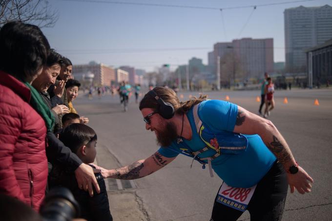 Les Nord-Coréens massés sur les trottoirs encouragent les coureurs, et lèvent la main pour taper celle des sportifs et posent pour des selfies.