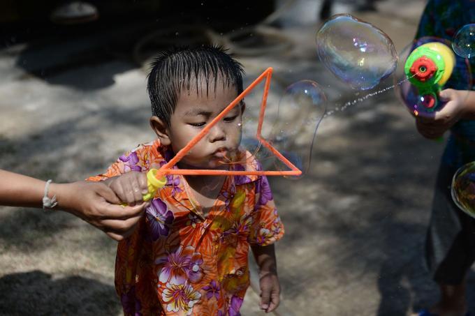 Un petit garçon souffle des bulles de savon.