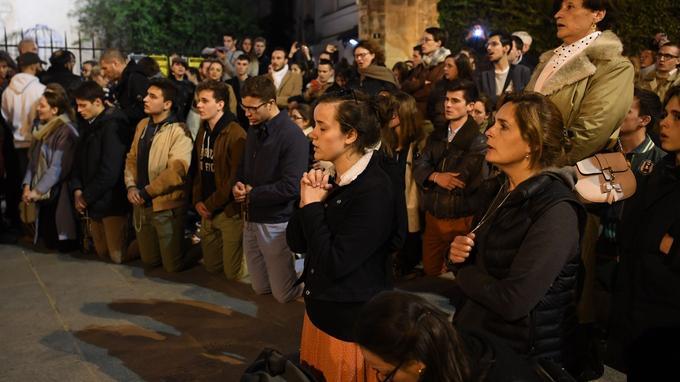 Des passants ont prié devant la cathédrale en feu.