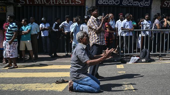 Un homme prie devant l'église de Colombo.