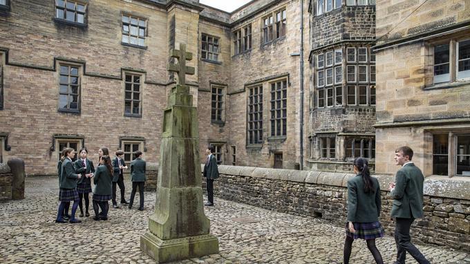Des élèves se retrouvent dans le Quadrangle, une cour intérieure historique ornée de la croix de Saint-Omer, érigée en hommage aux 21 anciens étudiants tués parce qu'ils étaient prêtres catholiques.