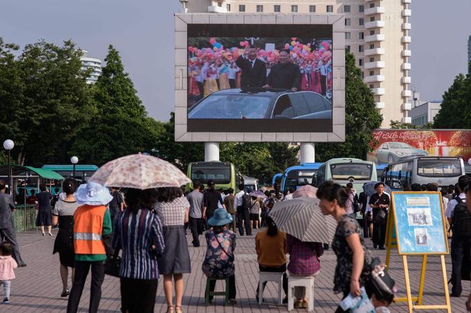 Des passants s'arrêtent sur une place publique pour regarder un écran géant diffusant les images de la visite de Xi Jinping à Pyongyang.