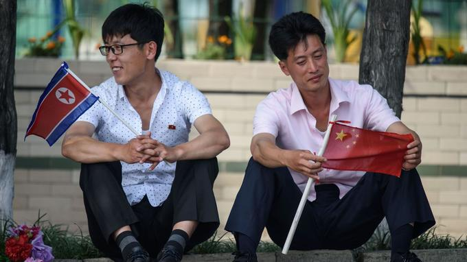 Deux hommes dans les rues de Pyongyang avant le passage de Xi et de Kim Jong-un.