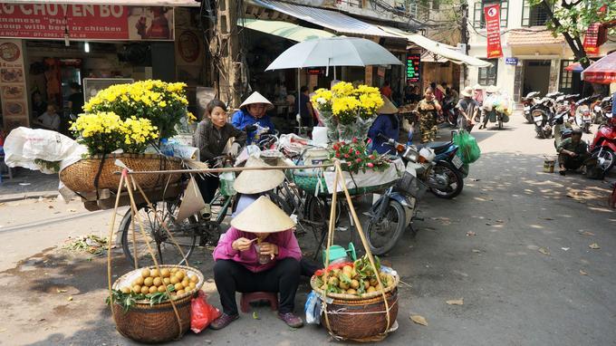 Dans le centre de Hanoï, des vendeuses de fleurs fraîches et de sapotille, fruit exotique aux allures de pomme.