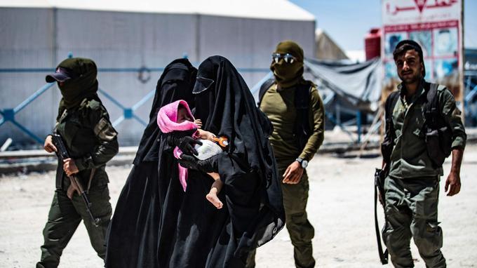En Syrie, le 23 juillet, des soldats de la coalition escortent des femmes présumées de Daech.