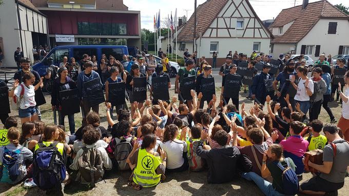 Les activistes font face aux fausses forces de l'ordre devant la Maison de la Citoyenneté, à Kingersheim.