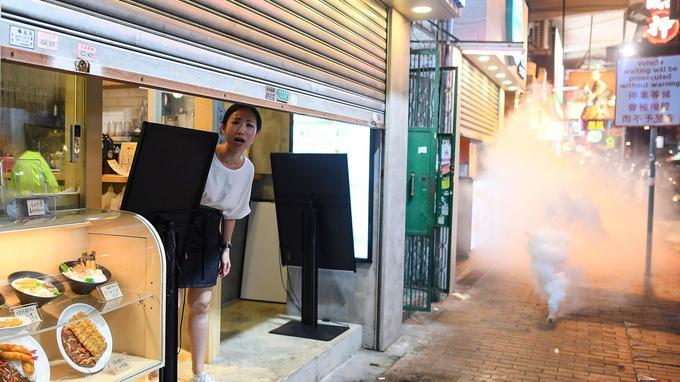 Une femme paraît apeurée alors que de nombreux tirs de gaz lacrymogène ont retenti ce mercredi soir à Hongkong.