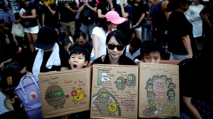 Une mère défile avec ses enfants et des pancartes où figurent des dessins illustrant des violences policières. <br/>