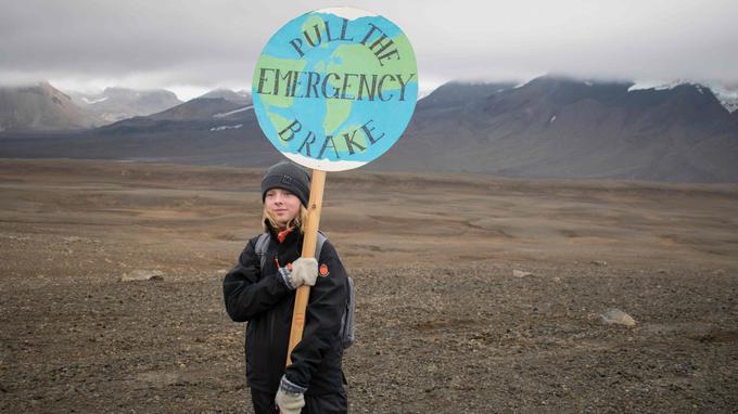 Une jeune fille islandaise venue participer à l'inauguration de la plaque en mémoire du glacier Okjökull. Sur son panneau représentant la Terre, on peut lire le message suivant: «Tirez sur le frein à main».