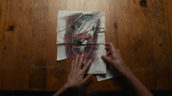 L'institutrice recompose un dessin sur lequel on devine un enfant dans la gueule d'une bête féroce.