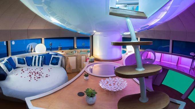 Un lit large et rond est installé au cœur de l'habitacle, ainsi qu'un salon aux fauteuils en cuir aux formes arrondies, face à un écran ouvert sur les profondeurs marines.
