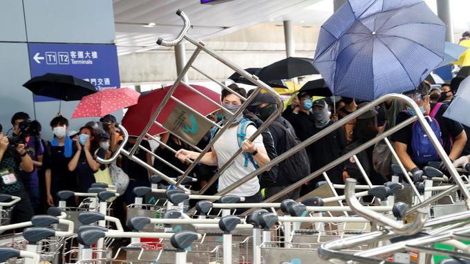 Des manifestants construisent des barricades à l'extérieur des terminaux de l'aéroport international de Hongkong.