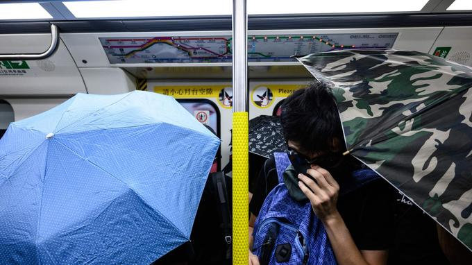 Des manifestants tiennent des parapluies ouverts à l'intérieur du métro lors d'une manifestation de perturbation à Hongkong.