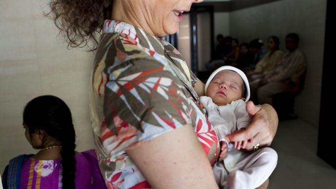 Une mère européenne berce son bébé, né d'une mère porteuse, en Inde.