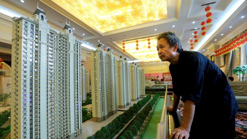 A visitor looks at a model of a new apartment complex in Wuhan