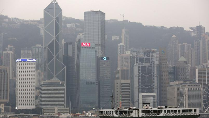 FILE PHOTO: A ferry sails at Victoria Harbour in front of the financial Central district in Hong Kong