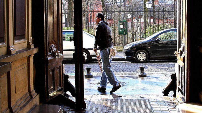 Un gardin en train de nettoyer un hall d'entrée d'un immeuble parisien, photo d'illustration.