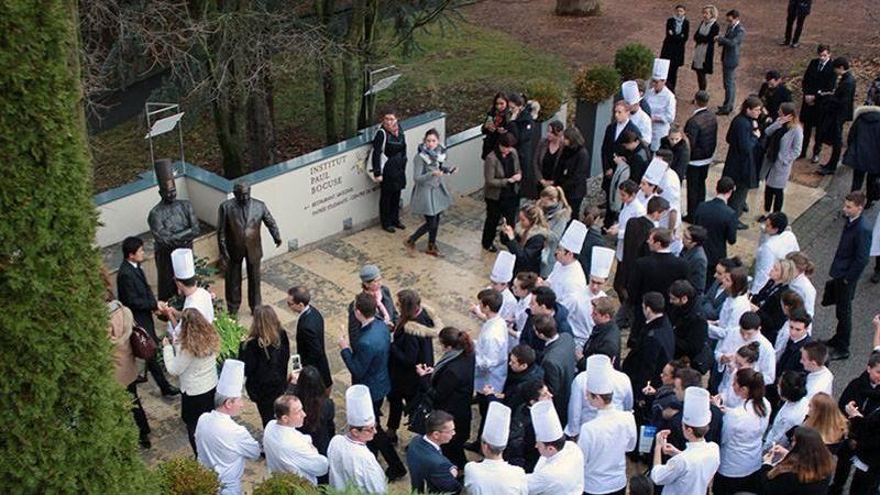 Les étudiants et professeurs sont réunis autour de la statue des deux fondateurs de l'école.