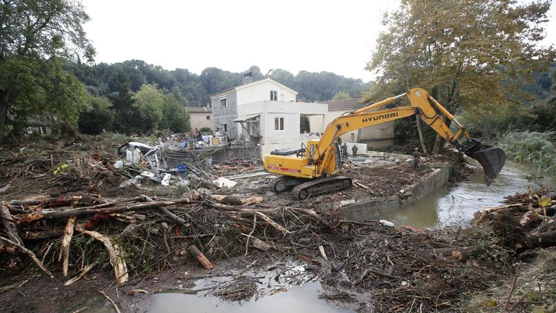 A mechanical digger clears away debris from trees in a stream near a house the day after torrential rains caused flooding in Biot