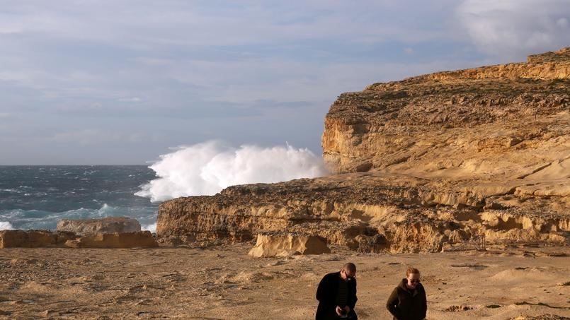 Tourists walk away after viewing the site where the natural structure known as the Azure Window collapsed, after the Maltese islands were hit by rough seas and stormy weather, at Dwejra on the island of Gozo