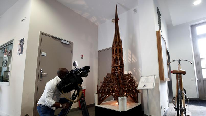 A cameraman films a model of the spire of Notre-Dame cathedral at the Les Compagnons du Devoir headquarters in Paris