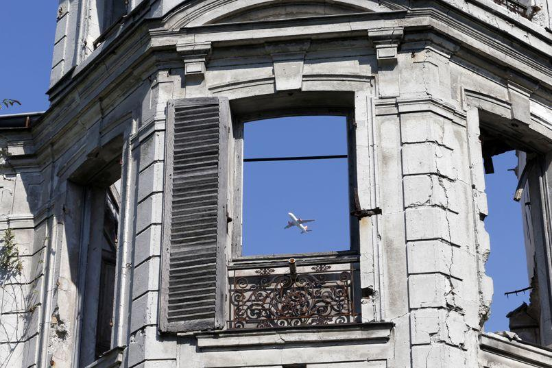 A commercial airliner flies over an abandoned 19th century manor in Goussainville-Vieux Pays, north of Paris