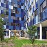En se rapprochant du cœur de l'ensemble de bâtiments, le pavage vitré en dégradés de verts évoquant le camouflage laisse la place à un camaïeu de bleus.