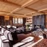 La confortable pièce de vie du chalet de Gstaad qui dispose de 7 chambres, d'un sauna, d'un hammam et d'une salle de fitness.