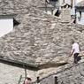 Dans le quartier du vieux bazar, des ouvriers réparent les toits.