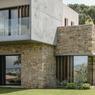 Parée de pierres d'anciennes restanques et surmontée d'une boîte en béton brut teinté, la maison se révèle en harmonie avec son environnement.
