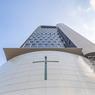 Vue en contre-plongée avec la croix vitrée éclairant l'église.