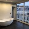 Une chambre avec vue sur les toits de Paris et baignoire.