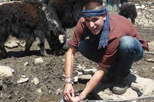 Joseph fait la vaisselle dans l'abreuvoir des yaks dans l'Himalaya (Népal) - Crédits: Joseph Parisot