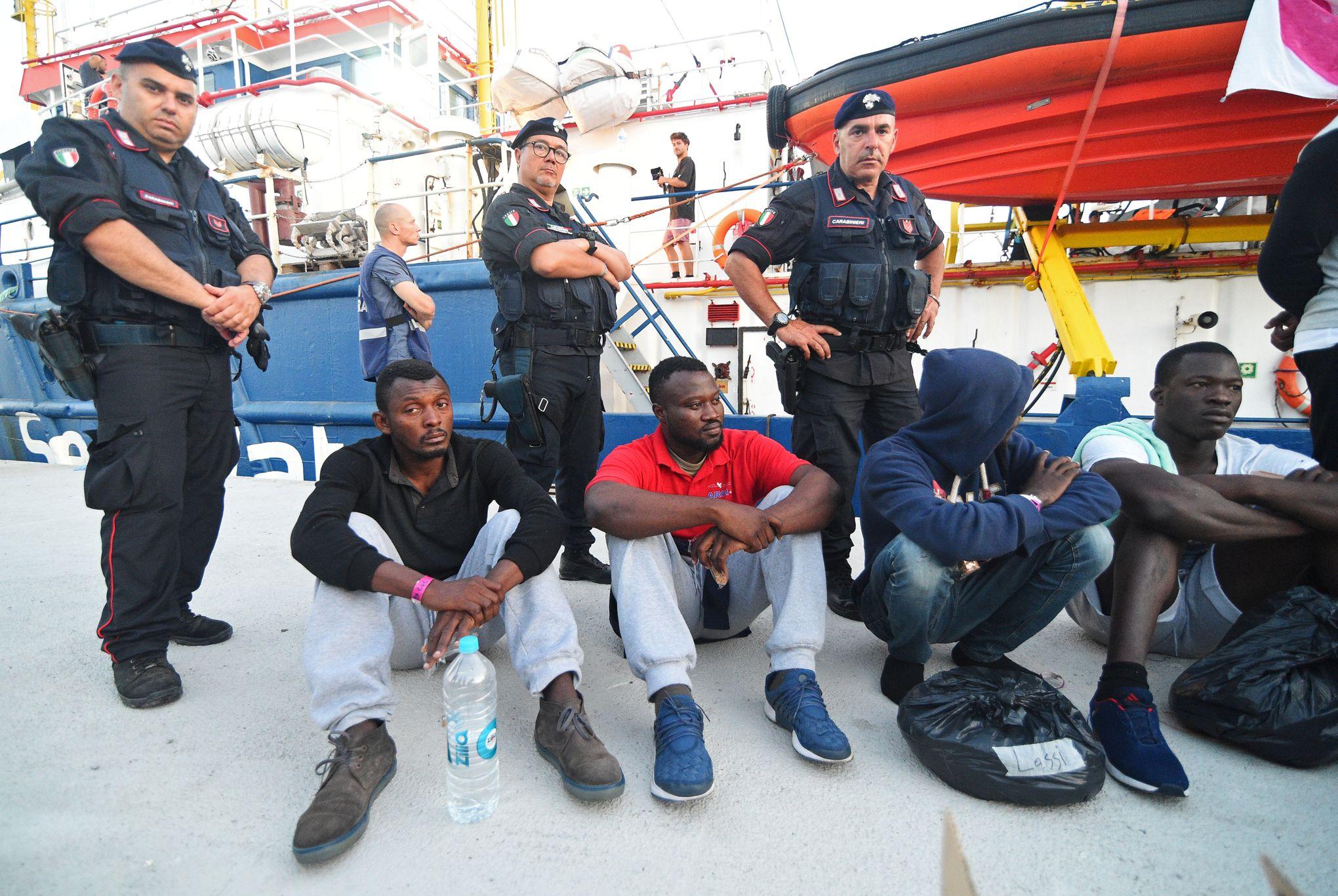 """Résultat de recherche d'images pour """"Des policiers italiens aux côtés de migrants après leur débarquement du navire Sea-Watch 3 à Lampedusa dans la nuit de vendredi à samedi"""""""