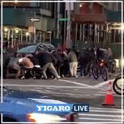 Des passants aident une personne coincée sous une voiture à New York