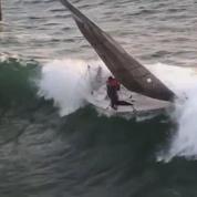 Une vague fait chavirer un petit voilier