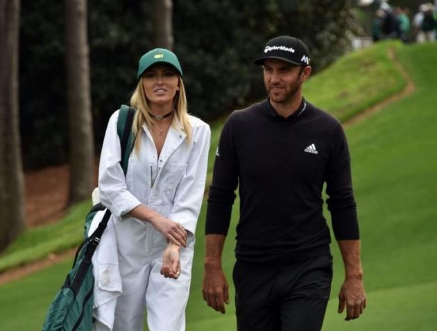 Le golfeur américain Dustin Johnson marche avec Paulina Gretzky, sa compagne, fille de l'illustre hockeyeyr canadien, pendant le concours de Par 3 avant le début du 80e Masters.