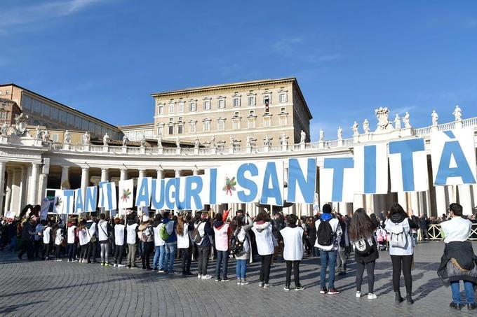 Des fidèles brandissent des pancartes formant les mots