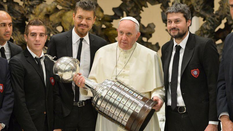 Le pape François tenant le trophée de la Copa Libertadores aux côtés de membres du club argentin de San Lorenzo, le 20 août 2014 au Vatican.