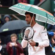 Novak Djokovic se promène sur le Central... sous un parapluie