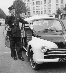 Policier téléphonant depuis une Renault 4CV en 1955.