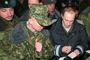 Vladimir Poutine signe des autographes, lors d'une visite surprise aux forces russes en Tchétchénie, le 1er janvier 2000.